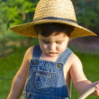 Little baby boy gardener watering the grass in serious fashion — Stock Photo