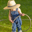 Little baby boy gardener playing in his front yard with the hose — Stock Photo