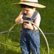 Royalty-Free Stock Photo: Little baby boy gardener playing in his front yard with the hose