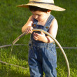 Little baby boy gardener playing in his front yard with the hose — Stock Photo #8663720
