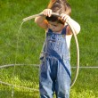 Little baby boy gardener playing in his front yard with the hose — Stock Photo #8663887