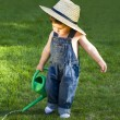 Sweet little baby gardener caught in the moment - Stock Photo