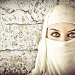 Woman dressed in Arab costume, rusty wall in the background — Stock Photo #8664386