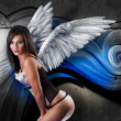 Beautiful young woman with white wings against graffiti wall. — Stock Photo