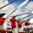 Soldiers firing their muskets in a battlefield - Stock Photo
