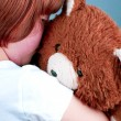Beautiful redhead girl hugs a teddy bear. — Stock Photo