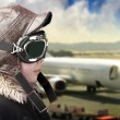 Boy playing with pilot hat and airport background — Stock Photo #8668365