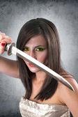 Beautiful female warrior holding katana sword — Stock Photo