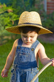 Little baby boy gardener watering the grass in serious fashion — Стоковое фото