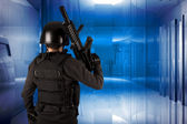 Armed man in protective cask with a machine gun on the modern bu — Stock Photo