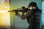 Street Assault, riot police firing his submachine gun — Stock Photo