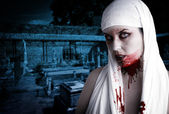Female vampire with blood stains in a cemetery. Gothic Image hal — Stock Photo