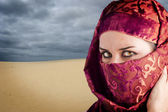 Woman dressed in Arab costume, desert in the background — Stock Photo
