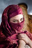 Mujer vestida en traje árabe, castillo en el fondo — Foto de Stock