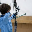 Young boy poised with bow and arrow — Stock Photo #8753029