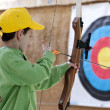 Young boy poised with bow and arrow - Stock Photo