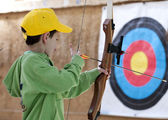 Young boy poised with bow and arrow — Stock Photo