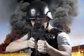 Person, explosion in an industry, armed police wearing bulletpro — Stock Photo