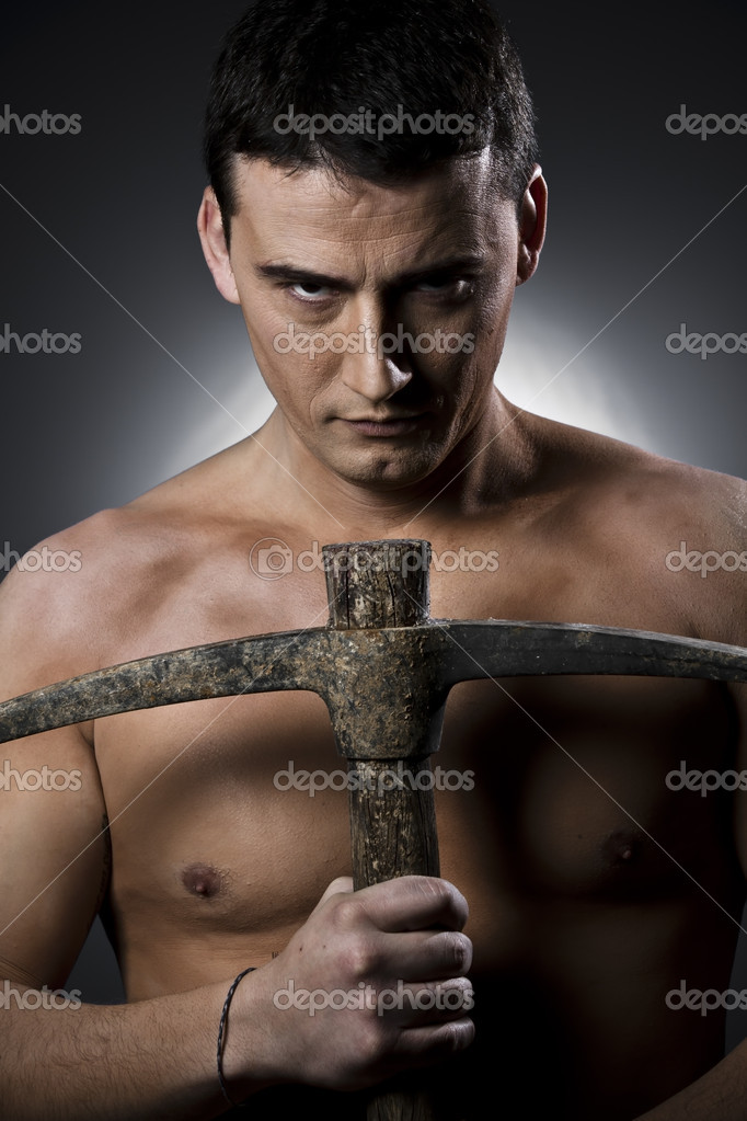 Topless construction worker with pick axe  over grey background  Stock Photo #9477365