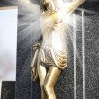 Jesus Christ on stone cross with mystic rays of light - Stock Photo