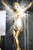 Jesus Christ on stone cross with mystic rays of light — Stock Photo