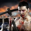 Male zombie in a cemetery, undertaker with pick axe - Stock Photo