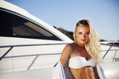 The young woman in a bathing suit has a rest on a deck of a yacht — Stock Photo