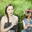 A girl with a baby in a field with dandelions — Stock Photo