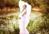 Hermosa mujer embarazada en un campo de diente de león — Foto de Stock