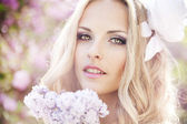Beautiful woman with flowers of lilac. Skincare — Стоковое фото