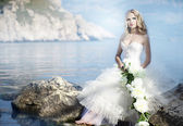 Bride with flower at the ocean — Stock Photo