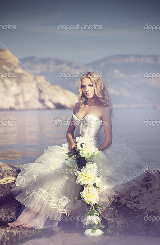 Bride with flower at the ocean — Stock Photo #10629529