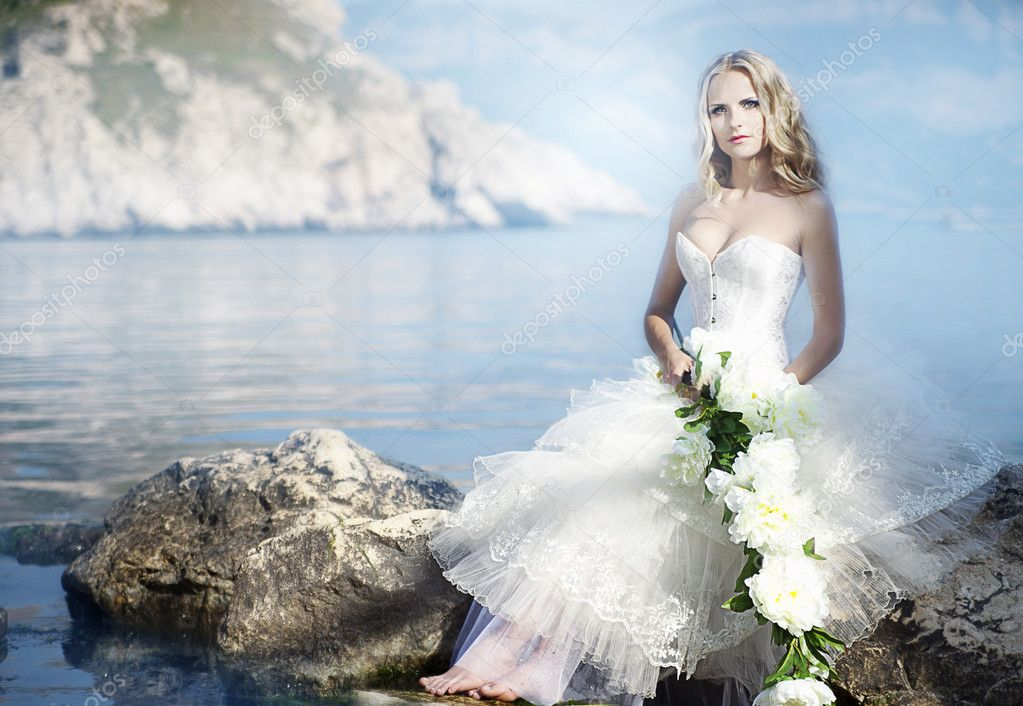 Bride with flower at the ocean — Stock Photo #10629535