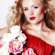The beautiful girl in a long red dress holds an exotic flower in a hand — Stock Photo #8640283