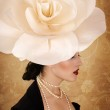 Beautiful girl with a hat on the head of the roses — Stock Photo