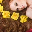 Beautiful woman laying in red bed with flowers in her hair — Stock Photo
