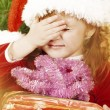 Adorable little girl wearing Santa Claus clothes with gift — Stock Photo