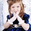 Beautiful brunette child in dress. Blue background. — Stock Photo