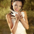 Pretty girl holding a white dove — Stock Photo