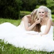 Young bride whispers to friend - Stock Photo