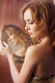 Young woman looking in mirror — Stock Photo