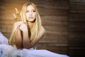 Girl with a candle in a dark room — Stock Photo