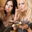 Stock Photo: Two girls eating cake in bed