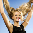 Portrait of beauty blonde woman against the blue sky background — Stock Photo #9595656
