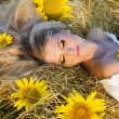 The beautiful girl lies on a haystack with sunflowers — Zdjęcie stockowe