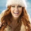 Smiling attractive woman in winter fur hat close-up studio portrait on white — Stock Photo #9596112