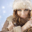 Smiling attractive woman in winter fur hat close-up studio portrait on white — Stock Photo