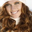Smiling attractive woman in winter fur hat close-up studio portrait on white — Stock Photo #9596133