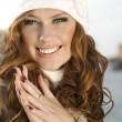 Smiling attractive woman in winter fur hat close-up studio portrait on white — Stock Photo #9596147