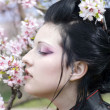 Royalty-Free Stock Photo: Artistic portrait of japan geisha woman with creative make-up near sakura tree in kimono